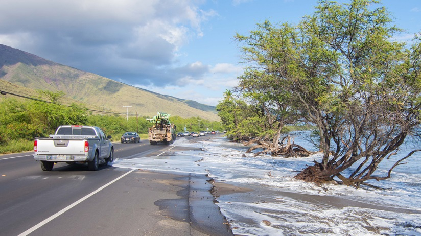 waves cross the highway during a king tide on maui