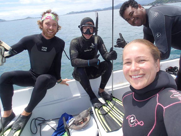 Graduate students in boat prepare to dive in the bay for science.