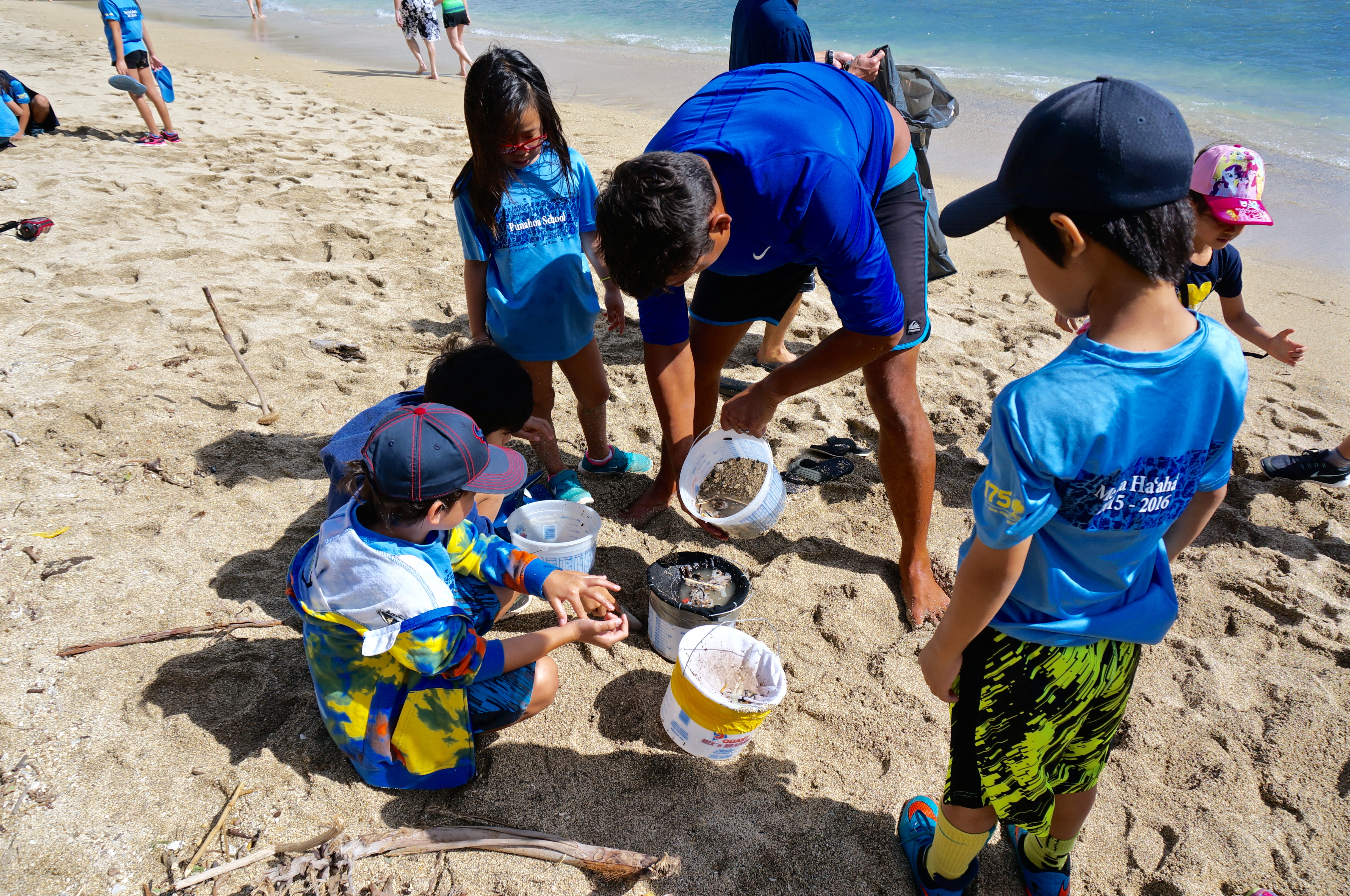students removing microplastics cleaning beach using buckets