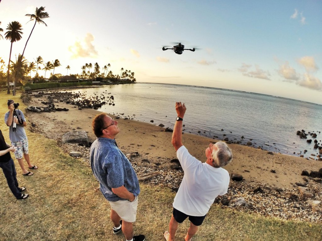 Researchers on a beach release a drone into the air