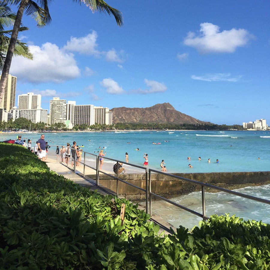 A view of one part of Wakiki Beach with a walkway, beach, swimmers, buildings, and Diamond Head all in view.
