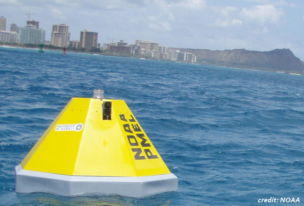 A bright yellow buoy floats on blue water in the foreground with buildings and Diamond Head crater as a back drop