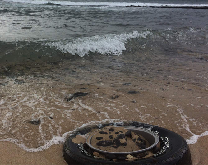 An old tire sits at the edge of the surf zone