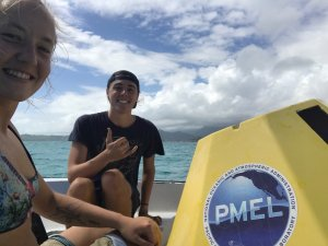 Image shows two students, grinning at the camera, with a buoy in a small boat on the water