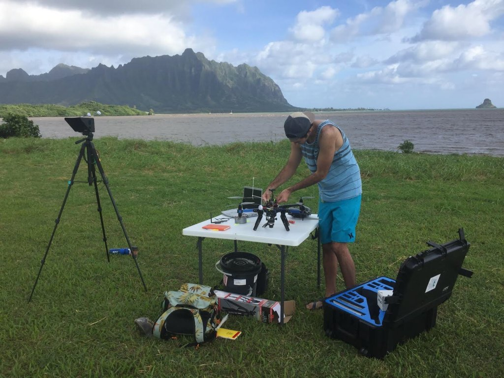 Student attaches instruments to a drone on a table in a field overlooking the bay.
