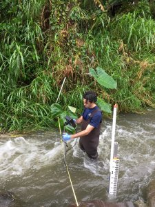 Student stands in turbulent stream taking measurements on an instrument