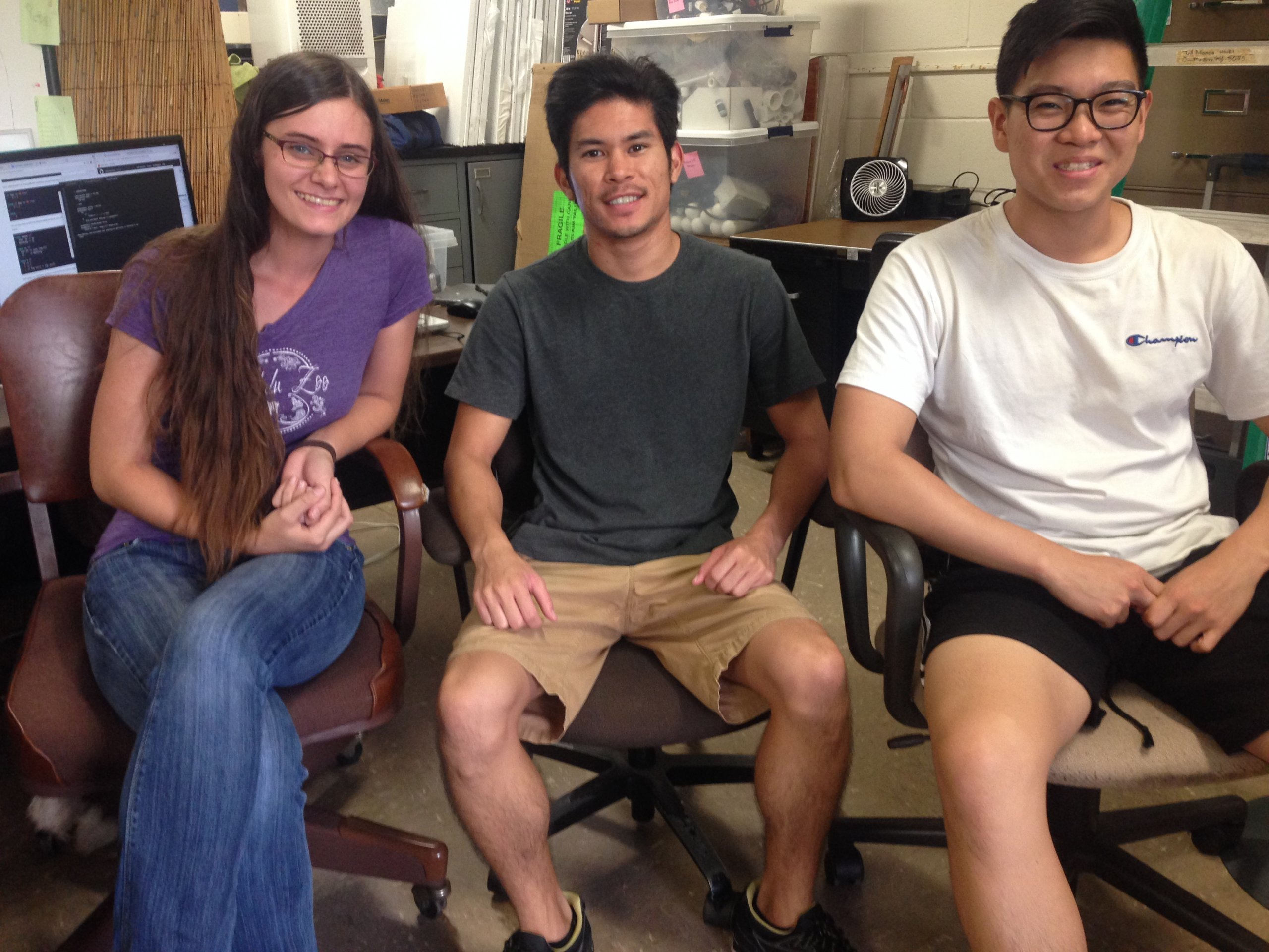 three students sitting in office chairs